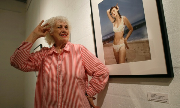 FILE - In this April 23, 2013 file photo, photographer Bunny Yeager poses next to a self portrait photograph taken in 1952 at the Bunny Yeager Studio in Miami. Yeager, a model turned photographer who was most famous for photographing Bettie Page in the 1950s, died Saturday, May 24, 2014, at a Delray Beach hospice. She was 85 years old. (AP Photo/Lynne Sladky, File)